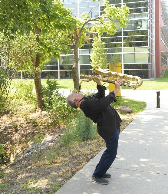 Denis DiBlasio playing the sax while standing and his back arched back