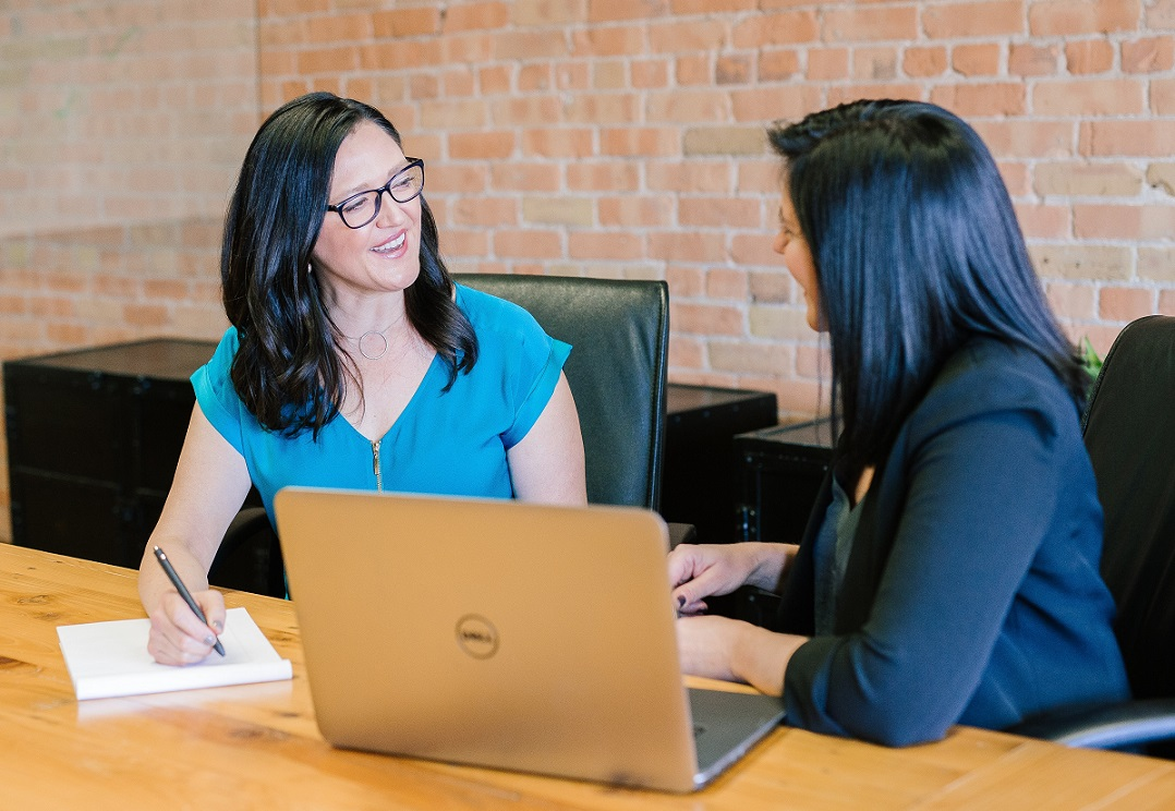 two women talking at a conference table; one has a laptop, the other is taking notes